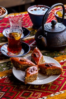 Side view traditional azerbaijani sweetness baklava with nuts with a glass of tea