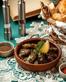Side view of traditional dolma in grape leaves in clay bowl