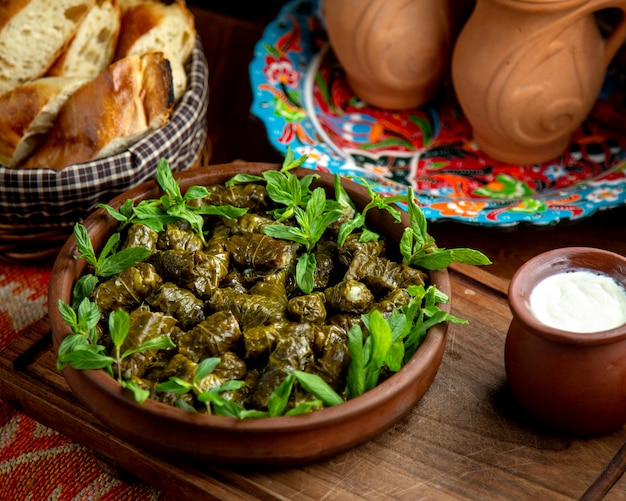 Side view of traditional dolma in grape leaves with sour yogurt on a wooden table