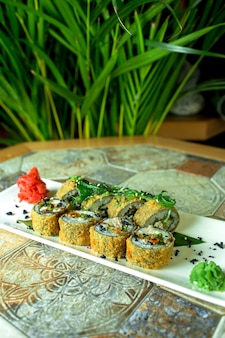 Side view of traditional japanese cuisine tempura fried sushi rolls with eel served with teriyaki on green