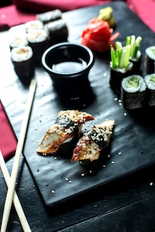 Side view of traditional japanese cuisine unagi eel nigiri sushi served with soy sauce on black board