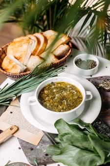 Side view of traditional russian green borsch with sorrel meat and eggs on a wooden board