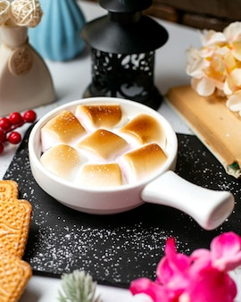 Side view of traditional thanksgiving dish sweet potato casserole with marshmallows in portioned forms on a wooden black cutting board