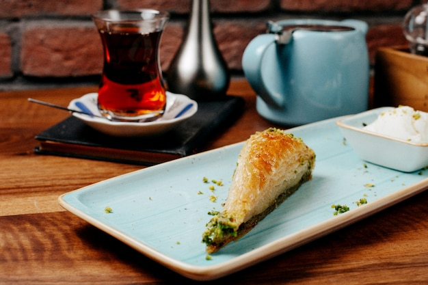 Side view traditional turkish dessert pistachio baklava with ice cream with a glass of tea