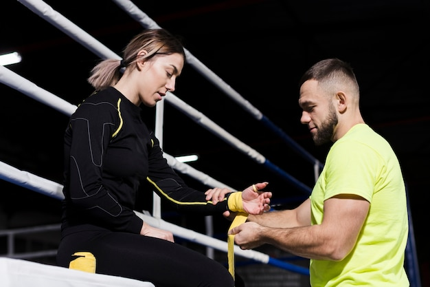 Side view of trainer and female boxer preparing for practice