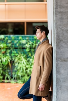 Side view of trendy young man wearing coat and scarf leaning on a wall while looking away