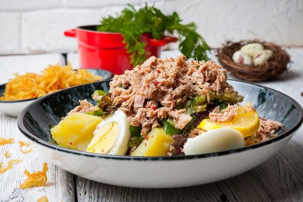 卵、ジャガイモ、木製のテーブルに卵とプレートの側面図マグロサラダ