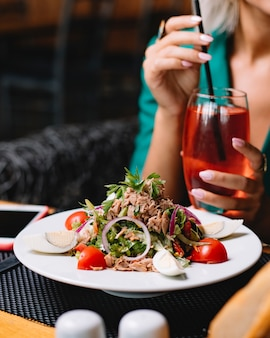 Side view of tuna salad with eggs onion cherry tomatoes topped with fresh parsley on a white plate with a woman sitting with cocktail at background