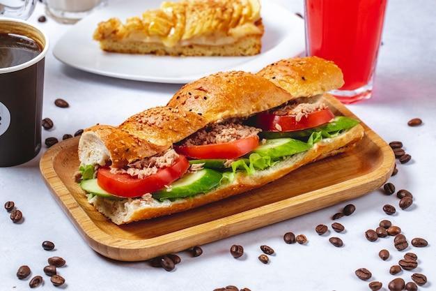 Боковой вид сэндвича с тунцом и белого хлеба с томатным салатом из огурцов и тунца и кофейных зерен на столе