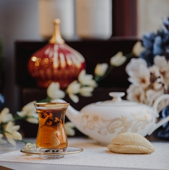 Side view of turkish azeri traditional pear-shaped glass for black tea armudu with shekerbura on the table