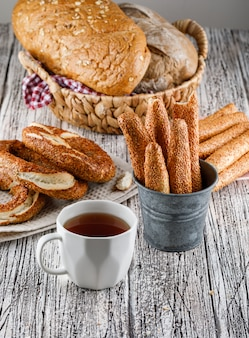 木製の表面に紅茶とパンのカップとサイドビュートルコベーグル。垂直