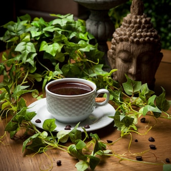 Side view turkish coffee with coffee beans and grape branch and statue head in cup on wooden table