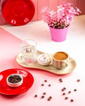 Боковой вид турецкого кофе с рахат-лукумом и стаканом воды