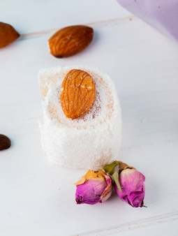Side view of turkish delights rahat lokum and tea rose buds on a white background