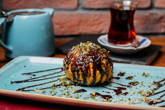 Side view of turkish dessert fried ice-cream covered with chocolate syrup on the table