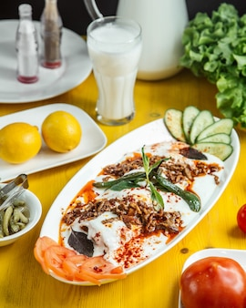 Side view of turkish iskender kebab served with sour yogurt sliced cucumbers and tomatoes on white plate