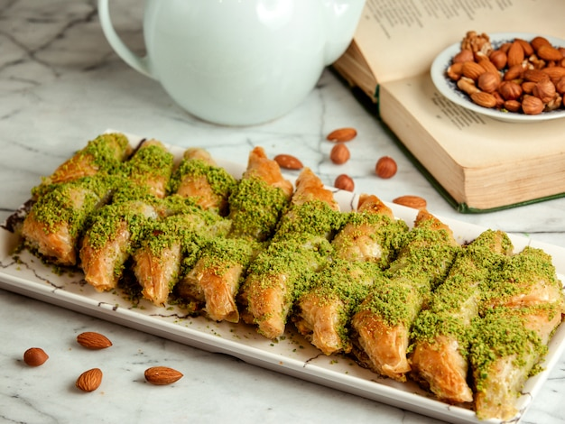 Side view of turkish sweets baklava with pistachio on platter