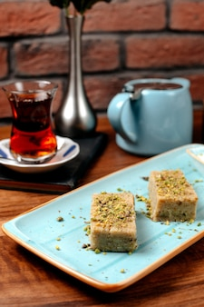 Side view of turkish sweets baklava with pistachio served with ice cream on platter