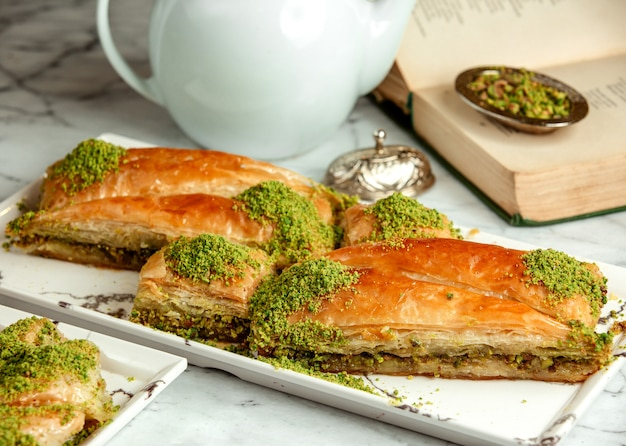 Side view of turkish sweets triangular shapedbaklava with pistachio on platter