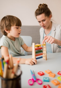 Side view of tutor teaching child how to use an abacus