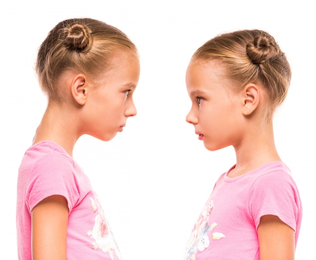 Side view of twin sisters are looking at each other.