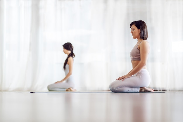 Side view of two calm attractive caucasian girls in thunderbolt yoga position.