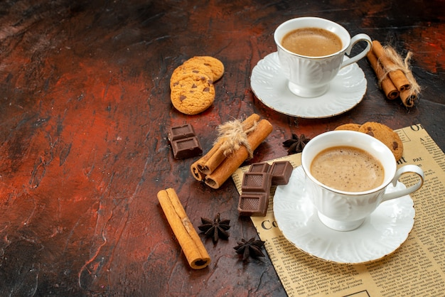 Side view of two cups of coffee cookies cinnamon limes chocolate bars on an old newspaper on the left side on dark surface