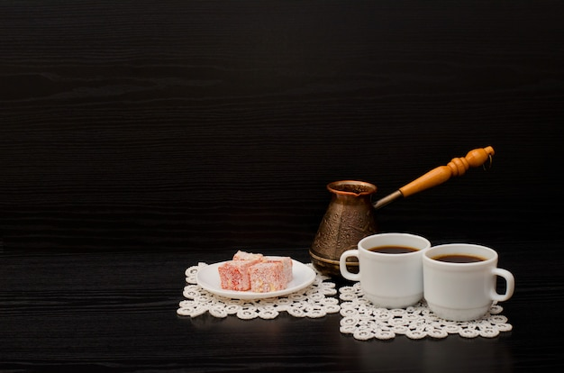 Side view of two cups of coffee on the lace napkins, turkish dessert and pots