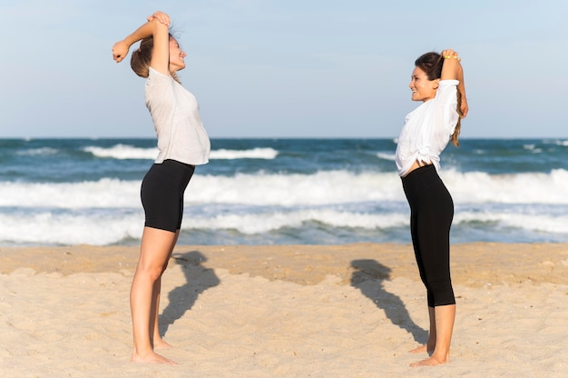 Side view of two female friends exercising on the beach