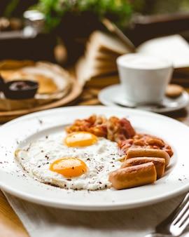 Вид сбоку два жареных яйца с сосисками, фасолью и беконом на тарелке