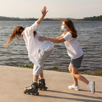 Side view of two friends having fun with roller blades by the lake