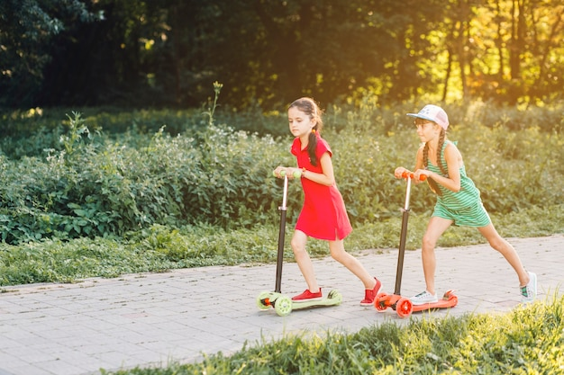 Side view of two girls riding push scooter on pavement in the park