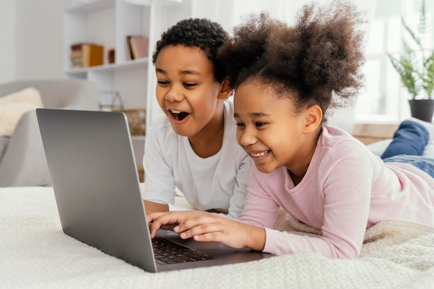 Side view of two siblings at home together playing on laptop