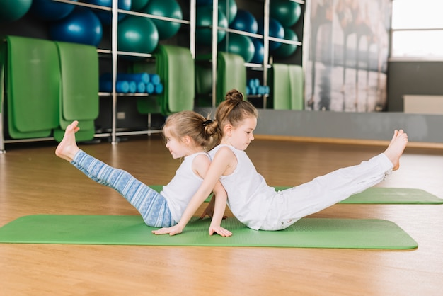 Side view of two small girl child doing yoga exercises