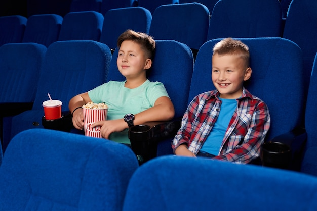 Side view of two smiling boys watching comical movie together in empty cinema. male friends holding popcorn and sweet water. children laughing and having rest on weekend