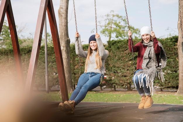 Вид сбоку две улыбающиеся молодые женщины на качелях