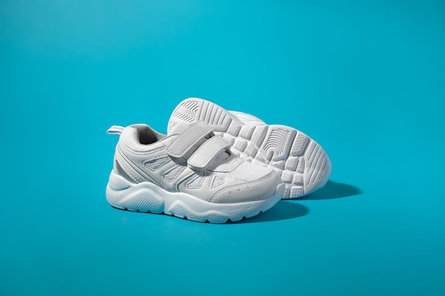 Side view of two white teen sneakers with velcro standing in front of the sole of another sneaker on...