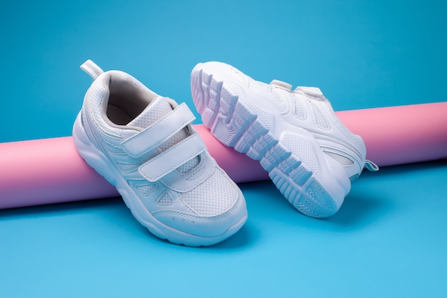 Side view of two white unisex running shoes on a pink long paper tube on a blue background one runni...