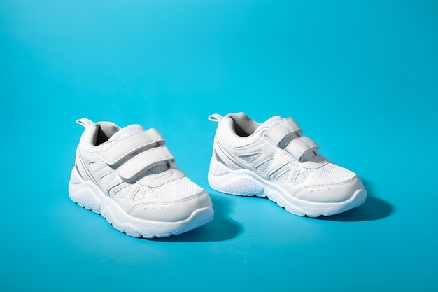 Side view of two white unisex sneakers with velcro fasteners for quick shoeing on a blue paper backg...