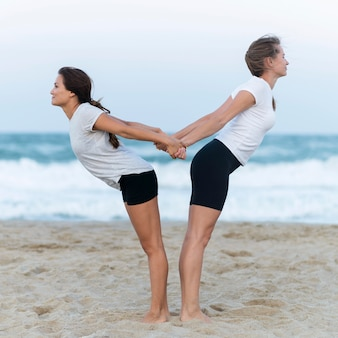 Side view of two women stretching on the beach