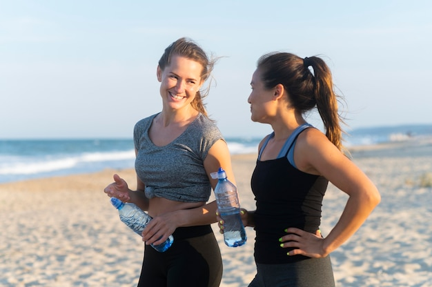 Side view of two women with water bottles during beach workout