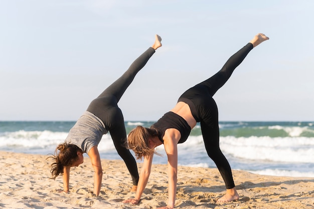 Side view of two women working out on the beach