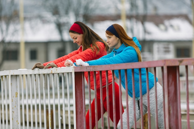 Side view of two young female friend standing near the railing