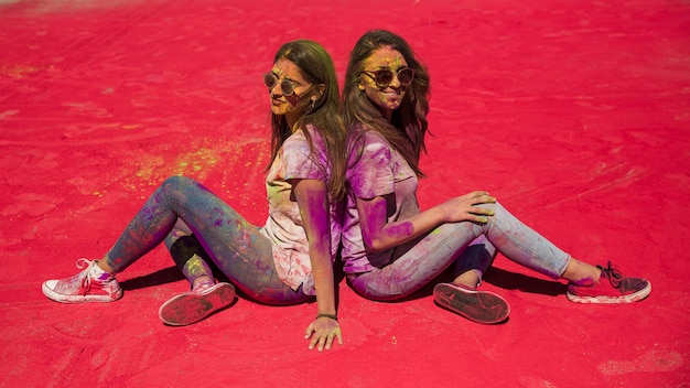 Side view of two young woman sitting back to back mess with holi color