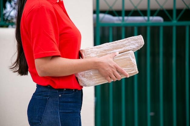 Vista laterale della postina irriconoscibile in berretto rosso che tiene i pacchi. corriere femmina ritagliata con camminare per strada e consegnare l'ordine espresso in scatole di cartone. servizio di consegna e concetto di posta