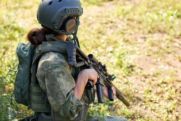 Side view on unrecognizable woman in military wear sitting on grass waiting for enemy at side