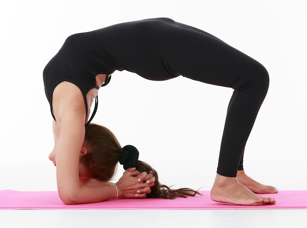 Side view of unrecognizable woman in sportswear doing urdhva dhanurasana pose variation while practicing yoga against white background