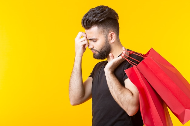 Side view of an upset tired young bearded stylish hipster man holding shopping bags posing on a