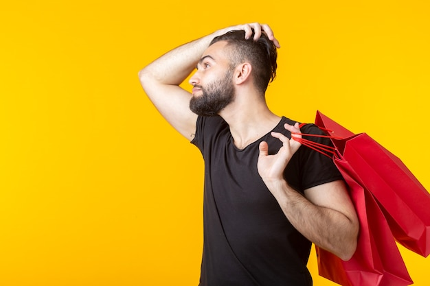 Side view of an upset young bearded stylish hipster man holding shopping bags posing on a yellow