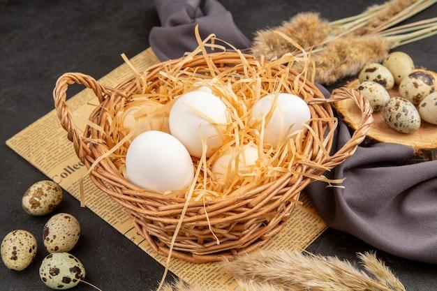 Vista laterale di varie uova organiche in un vaso marrone su una tavola di legno su un vecchio asciugamano nero a punta di giornale su superficie scura